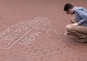 FILE PHOTO: MICHELLE XU/THE HOYA Ari Goldstein (SFS '18) chalks Red Square at a summer event geared toward garnering university administrators' attention on sexual assault.