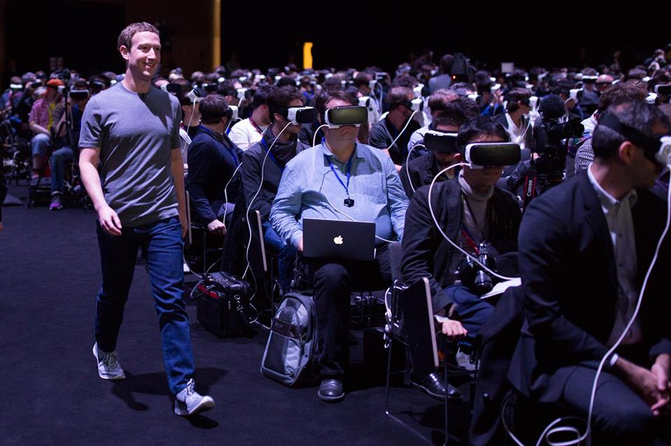 COURTESY MARK ZUCKERBERG FACEBOOK Facebook CEO and cofounder, Mark Zuckerberg strides past an audience wearing Occulus Rift Virtual Reality headsets.
